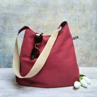 Burgundy upholstery canvas hobo shoulder bag pictured with white tulips and sunglasses