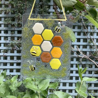 Fused glass three bees with dichroic wings on honeycomb hanger.