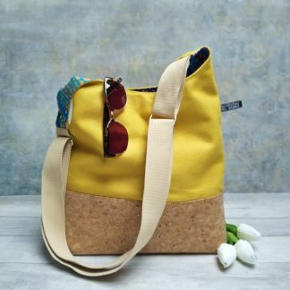 cork fabric and yellow wool fabric cross body bucket bag pictured with three tulips and a pair of sunglasses