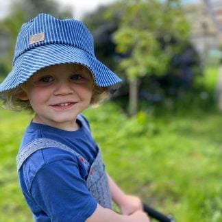 A child in a blue T shirt & dungarees outside in a garden wearing a striped denim bucket hat & smiling at the camera