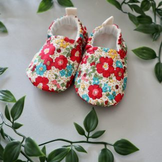 A pair of soft soled baby shoes in a red & multicoloured small floral print displayed with some green leaves in a natural style