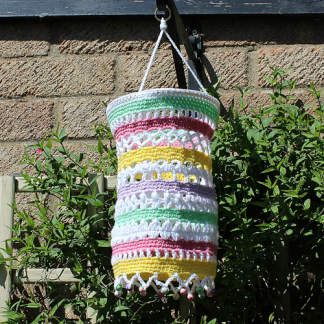 A crocheted garden lantern hanging from a bracket against greenery. It's colours are white, lilac, lime green, yellow, and pink. There are coloured beads around the bottom to match.