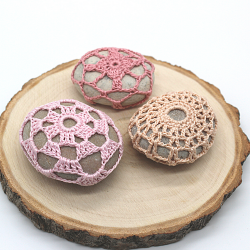 3 crochet covered pebbles,one in plae pink, one in rose pink and one in peach. They're arranged on a wood slice.