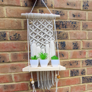 Macrame wall hanging with wooden shelf and little pots outdoor look