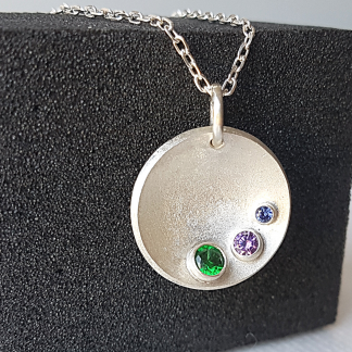 Circle pendant polished to satin is placed on the black display sponge.