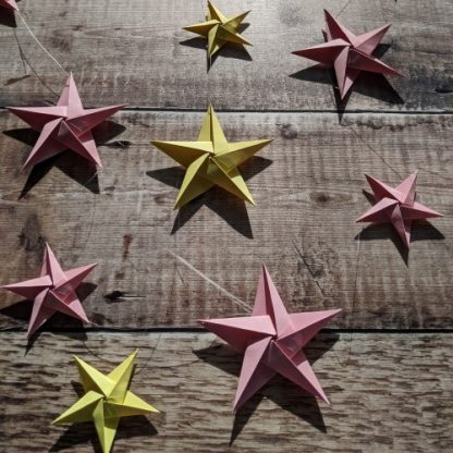 Pink and yellow paper stars in sunshine