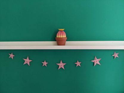 Pink paper stars bunting with rainbow origami cactus on shelf