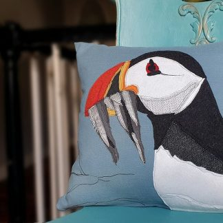 Blue cushion with appliqued Puffin and Sand Eels