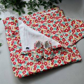 A red ditsy floral baby blanket & a pair of matching slippers