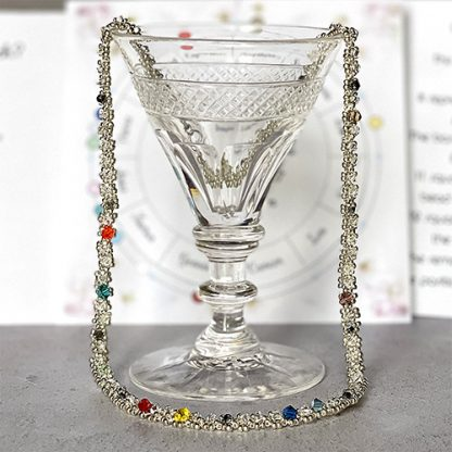 Wedding or anniversary astrology necklace over cocktail glass