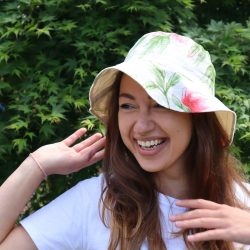 A girl with long brown hair wearing a sun hat in cream, pink & green floral fabric