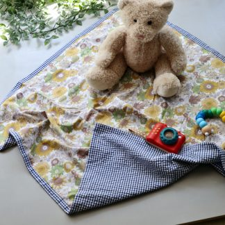 A yellow floral play mat with blue & white gingham edging shown displayed with a teddy bear & toy camera
