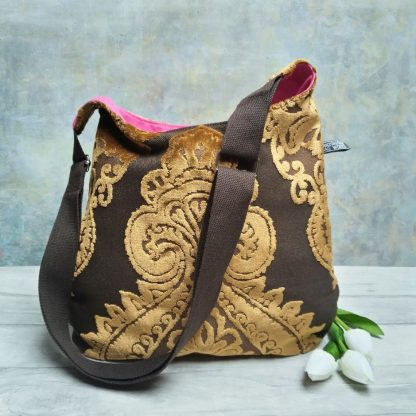 bronze and brown damask and pink lined hobo cross body bag pictured with three white tulips