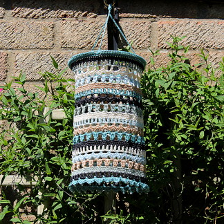 a hand made garden lantern in shades of teal, duck egg, cream,sand and charcoal. It has a scalloped edge with tiny beeds along it
