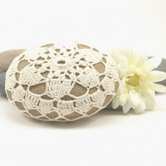 A brown stone which has been covered in cream crochet lace. There is a flower by the side of it and a piece of driftwood in the background