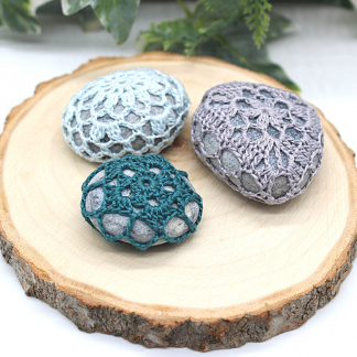 3 natural stones covered in crochet lace dsigns. There is one in teal, one in ice blue and one in grey. They are arranged on a natural wood slice and there is green foliage just visible in the background.