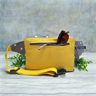 Grey polka dot oilcloth and Mustard wool bum bag pictured with sunglasses and foliage