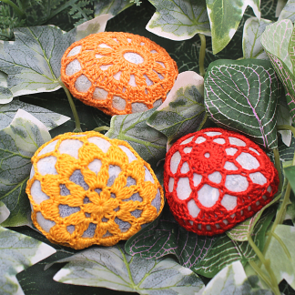 a set of three lerge pebbles covered in crochet. Each cover is different and there is one red, one orange and one tangerine. The backgrouind is leaves