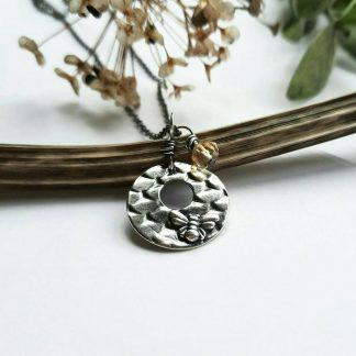 A handmade, textured, circular, washer style, oxidised fine silver pendant with a tiny bumble bee and a wire wrapped yellow citrine gemstone charm on a sterling silver chain, artisan handcrafted by The Tiny Tree Frog Jewellery