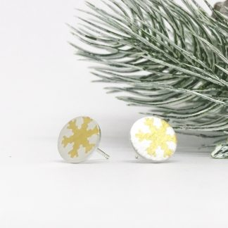 silver earrings with gold snowflake infant of christmas tree on a white background