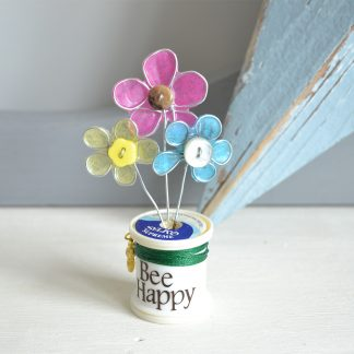Three wire flowers set in a cotton reel with the words Bee Happy to the front