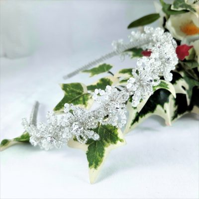 A bridal headband of beaded silver, crystal and pearl flowers