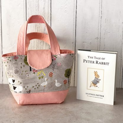 Farm animals toy tote bag beside book for size comparison