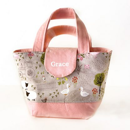 Toy shopping tote bag with farm animals print in pink personalised with name on tab
