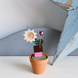 Miniature wood house sitting in a plant pot with glass heart and wood sun and the words Home is where love grows