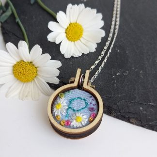 Hand embroidered mini hoop pendant with silver look chain. Personalised with the letter P and decorated with daisies and mini roses.