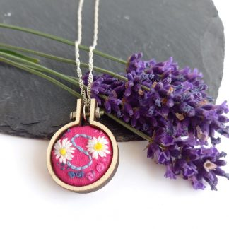 Hand embroidered mini hoop pendant with chain, personalised with the letter S. Daisies have been embroidered on bright pink cotton fabric.