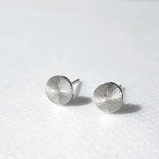 Circle silver earrings with a sun rays texture and mirror polish on a white background.
