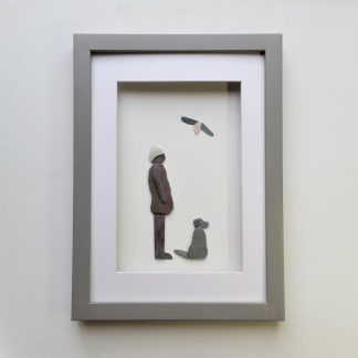 framed pebble art picture of a lady and dog with seagull flying overhead