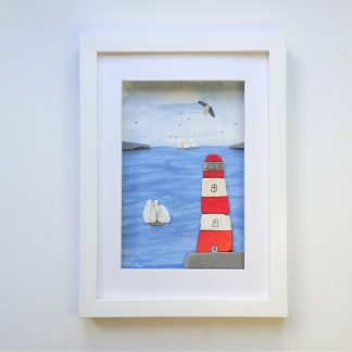 framed picture of a red and white lighthouse and tall ships made from sea pottery and sea shells