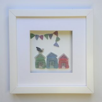 framed picture of three colourful stripy beach huts and bunting made from Cornish sea glass