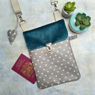 Teal velvet and grey polka dot oilcloth small cross body bag pictured with two cacti and a passport