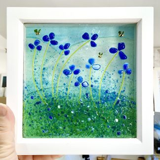 framed blue flowers art in hand to show size