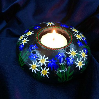 Round tea light holder with hand painted edelweiss and gentian violets on dark background with candle lit