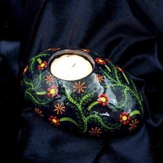 Oval tea light holder with dark blue background and red, orange, yellow and green flowers and leaves
