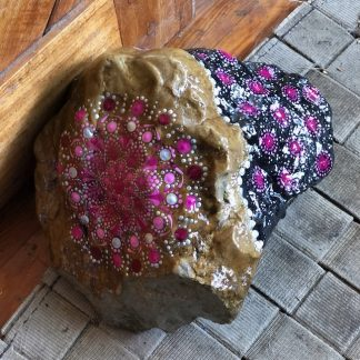 Natural Rock with dot mandala design hand painted in shades of pink and silver by a door
