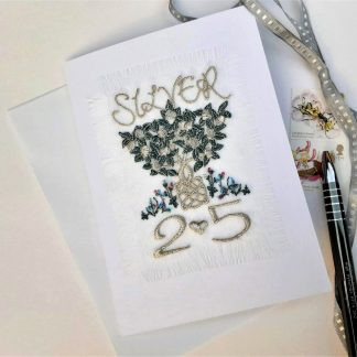 A tree of life with entwined root ball is the central motif on a greetings card that has the words SILVER and numbers 25 with a small heart all on a fringed textile mpanel applied to the front of a white greetings card, lieing next to a pen, decorative stamps and silver ribbon on a white background.le