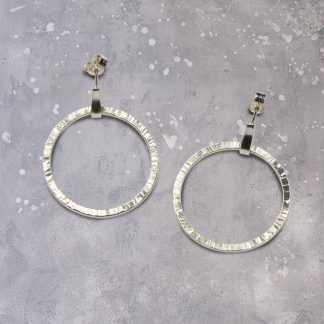 textured hanging hoop earrings showing the front view