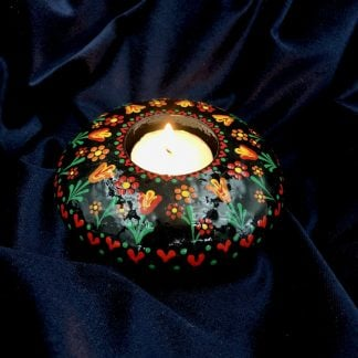Black tea light holder with brightly coloured tulips in red, orange and yellow with lighted candle