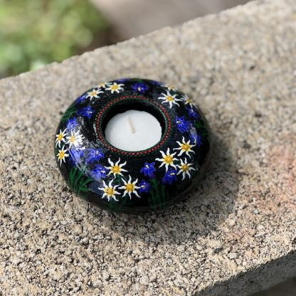 Round tea light holder with hand painted edelweiss and gentian violets on dark background on stone