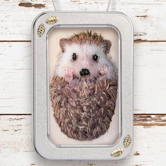 hedgehog fabric picture framed in a little tin