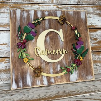 wooden block with hand painted thistles and flowers with an initial and a family name in the centre