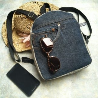 Mini backpack made from grey striped oilcloth and repurposed denim pictured resting on a sunhat with phone and sunglasses