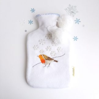 Snow white fleece hot water bottle coverand a 2 litre hot water bottle included. hand embroidered robin stood in snow with silver thread embroidered snowflakes falling. Two fluffy snowball pompoms tied at the neck with light blue blanket stitch at all edges.