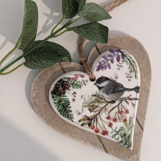 A two layer wooden hanging heart decoupaged with a bird sat amongst berries and wildflowers. Finished with a natural twine hanger.
