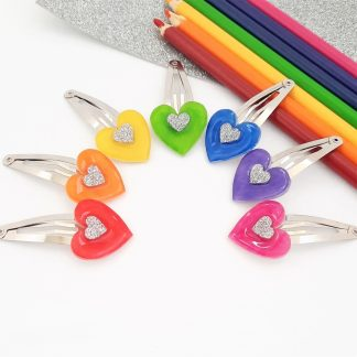Heart shaped hair clips in the colours of the rainbow each with a silver centre